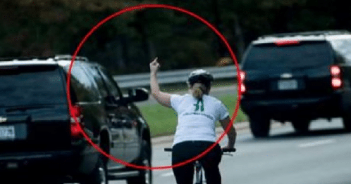 woman on bike rides up to trump motorcade and gives him the bird  what happens next goes viral
